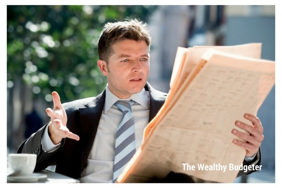 Businessman reading surprising money facts in the newspaper