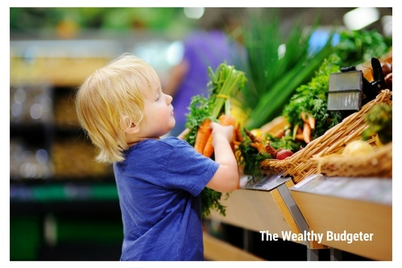 Little boy checking to see if fresh carrots fit within the grocery budget
